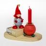 Filzmützen Tonttu, hölzerne Streichholzschachtel und Kerzenhalter auf Holzplatte